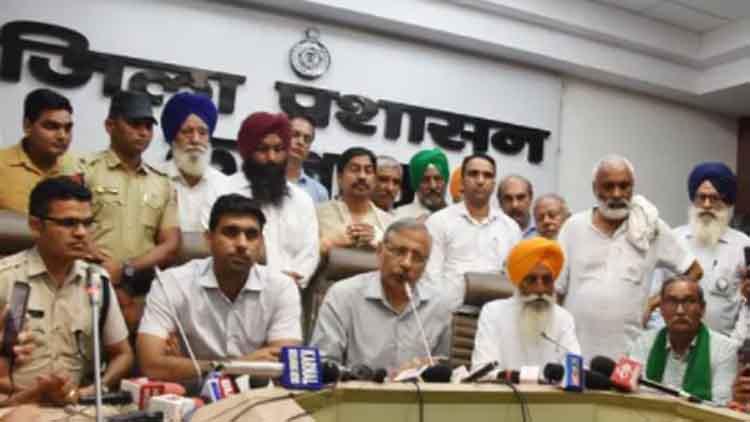 अधिकारी और किसान नेता प्रेसवार्ता संबोधित करते हुए