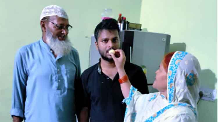 सैफुर रहमान को मुंह मीठा करवाते हुए उनके माता-पिता